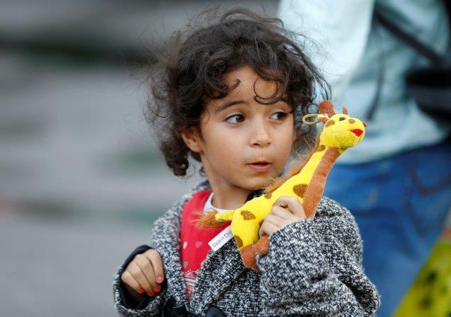 Child seeking asylum with giraffe toy